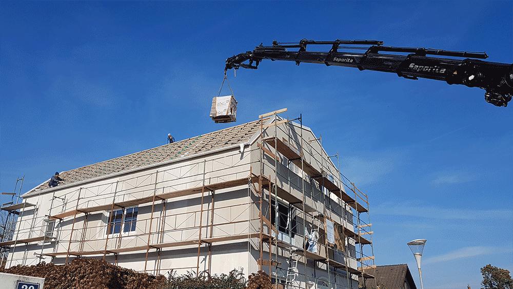 Dachdeckung: Ein Kran befördert die Dachziegel aufs Dach