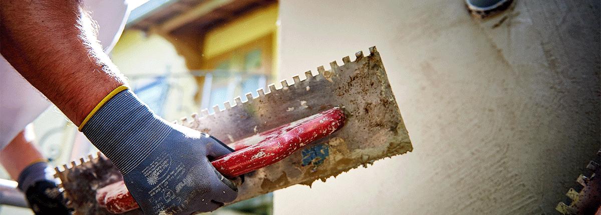 Ein Mitarbeiter verputzt die Fassade des Hauses