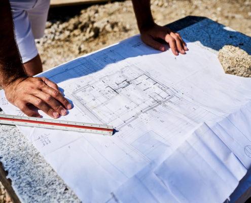 Auf der Baustelle wird der Bauplan von unserem Mitarbeiter überprüft